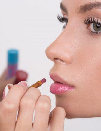 Makeup artist applies lipstick. Beautiful woman face. Perfect makeup